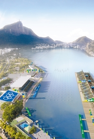 Bird's eye view of rowing lanes placed in a lagoon. There are bleachers around and a mountain in the background.