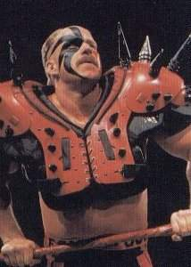 A man in face-paint wearing spiked shoulder pads looks off into the distance