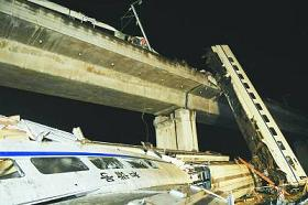 An image of the wreck; after the collision, four cars of the rear train fell off the Ou River bridge, slamming into the ground more than 20 m (66 ft) below