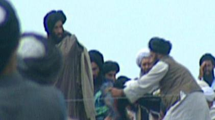 A still from a 1996 video taken secretly by BBC Newsnight. It purports to show Omar (left) presenting the cloak of Muhammad to his troops in Kandahar, before their victorious assault on Kabul.