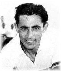 A man in a white shirt, smiling towards the camera