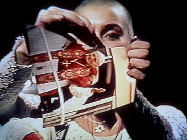 Sinead O'Connor tears a picture of Pope John Paul II apart during a live SNL performance Sinead rips into the Pope.jpg