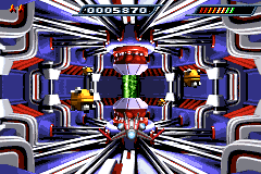 Bosses such as the Refusor usually have a single vulnerability—here, the green core. From top left, the number of lives remaining, score, and ship energy are shown.