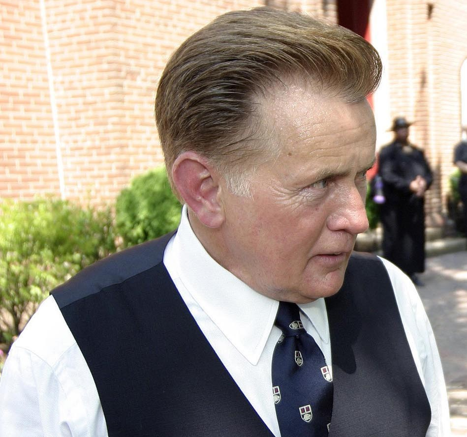 martin sheen putting on a jacket