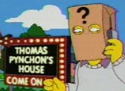 Cartoon frame showing a man with a paper bag over his head talking into a mobile phone. The bag has a large question mark printed on it and the man stands in front of a large illuminated sign in block letters which says 'THOMAS PYNCHON'S HOUSE – COME ON IN'