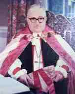 A poor-quality photograph of an old white man seated, wearing spectacles with thick black frames, robed in the vestments of an Anglican bishops: rochet and chimere, pectoral cross, and red-and-white cope; and holding a red-and-gold mitre