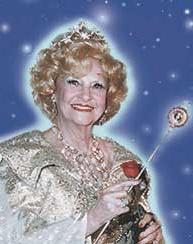 A smiling, framed, old woman with a wand, behind her the starry sky.