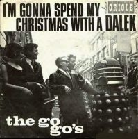 "A square record cover, with the text ""I'M GONNA SPEND MY CHRISTMAS WITH A DALEK"" and the label ""ORIOLE"" (smaller) above a photograph showing a young woman and four young men in 1960s dress smiling and laughing at a grey Dalek on an urban street. The white text ""the go-go's"" is superimposed on the lower left quadrant of the photograph."