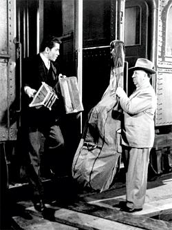 Alfred Hitchcock boards the train while lead character Haines gets off, at the beginning of Strangers on a Train in 1951