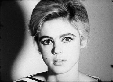 Black-and-white image of a woman with short light hair shown from the neck up against a light background. Her head fills the center of the image from top to bottom and casts a shadow on the background to her right.