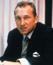 Davis wearing a dark suit and tie and sneering from behind a desk. Davis  circa 1970. Position: Owner