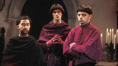 """Prince Edmund, Baldrick and Lord Percy in purplse clerical cassocks"""