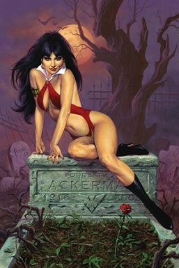 Vampirella reclining. She has dark black hair, red lips, and is wearing her red sling suit costume and black high heel boots