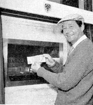 British actor Reg Varney using the world's first ATM in 1967, located at a branch of Barclays Bank, Enfield. The system was developed by De La Rue