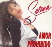 A Hispanic woman, who is wearing a black spandex that is underneath a golden-plain shirt, is tilting her head towards the viewer of the picture and posing; titled with the singer's name and song.