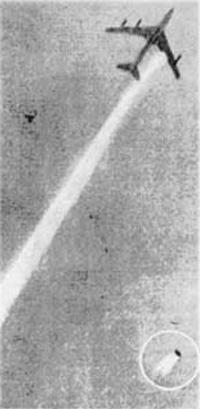 Фотография летящего самолета с падающим на землю двигателем.