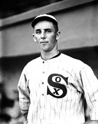 "A man in a white baseball uniform with dark pinstripes with ""SOX"" written on the chest and a baseball cap."