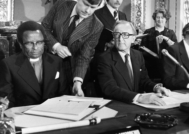 Bishop Abel Muzorewa signs the Lancaster House Agreement seated next to British Foreign Secretary Lord Carrington. Lancaster-House-Agreement.png