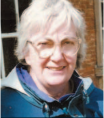 grey-haired woman wearing glasses and a teal coat