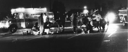 Several emergency personnel in a night-time scene, clustered around a person lying on the floor.