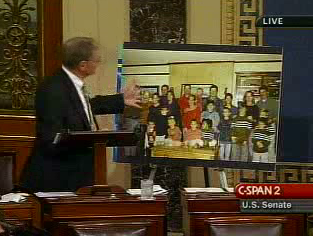 Inhofe pointing at a large photograph of his family, proclaiming none have been divorced or LGBT Inhofefamily-noglbt.png