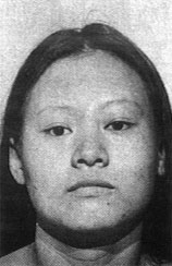 Mugshot of a woman: her face is broad and squarish, framed by long hair.