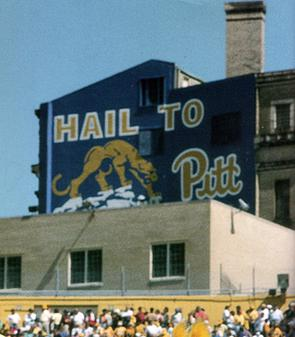 "Pennsylvania Hall, now demolished and replaced by a modern residence hall of the same name, from inside Pitt Stadium, also now demolished.  This side of Pennsylvania Hall shows the ""Hail to Pitt"" sign that existed in many variations throughout the years on the campus of the University of Pittsburgh. This version was painted for the 100th season of Pitt football in 1990. It depicts a stylized version of Giuseppe Moretti's Panther statues as well as the traditional script Pitt logo that served as the primary athletic logo from 1973 until 1997."