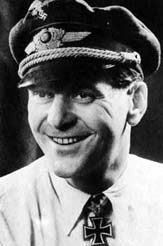 The head and shoulders of a young man, shown in semi-profile. He wears a peaked cap and shirt with an Iron Cross displayed at the front of his shirt collar. His hair appears dark and short, his nose is long and straight. He is smiling broadly; his eyes are looking to the left of the camera.