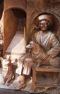 The Queen Mother Memorial bronze on The Mall, by Paul Day, shows her with two corgis.