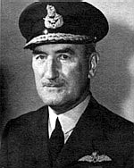 Head-and-shoulders portrait of man in dark uniform with peaked cap and pilot's wings on left-breast pocket
