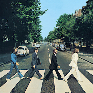 The cover of Abbey Road has no printed words. It is a photo of the Beatles, in side view, crossing the street in single file.