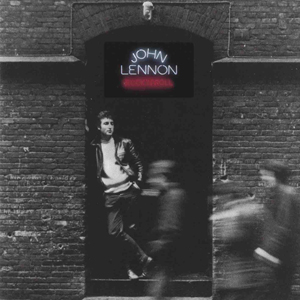 A black-and-white photo of Lennon leaning up against a brick wall
