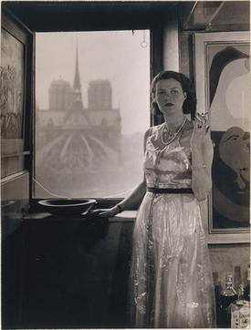 Peggy Guggenheim, Paris, c.1930, photograph Rogi André (Rosza Klein). In the background, Notre Dame de Paris, and on the right, Dutch Interior II (1928) by Joan Miró.