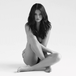 The deluxe edition cover features topless Selena Gomez covering her body with her arms and legs in black-and-white filter.