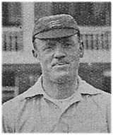 A black and white grainy image of the head and shoulders of a man. He is wearing a flat cricket cap, with three light horizontal swords visible, and a white top.