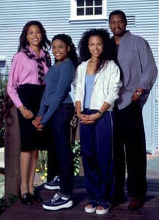 An image of an African-American family standing outside of a house.