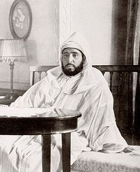 Sultan Abdelhafid seated on a settee behind a table