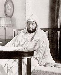 Sultano Abdelhafid sesila sur kanapo malantaŭ tablo