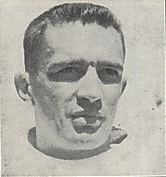 Black and white neck-up photograph of Akins in a football uniform