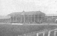 View towards one end of the ground, showing a roof, supported by several pillars and bearing a clock, covering the central part (behind the goal) of an otherwise open terrace
