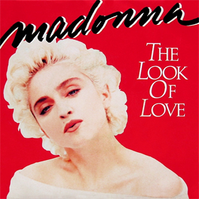 Madonna looks towards the front and tilts her head to the right. She is wearing a white dress, with bare shoulders.