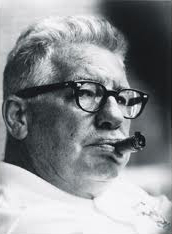 Candid black and white head-shot photograph of Rooney wearing a white shirt and black-rimmed eyeglasses chewing on an unlit cigar