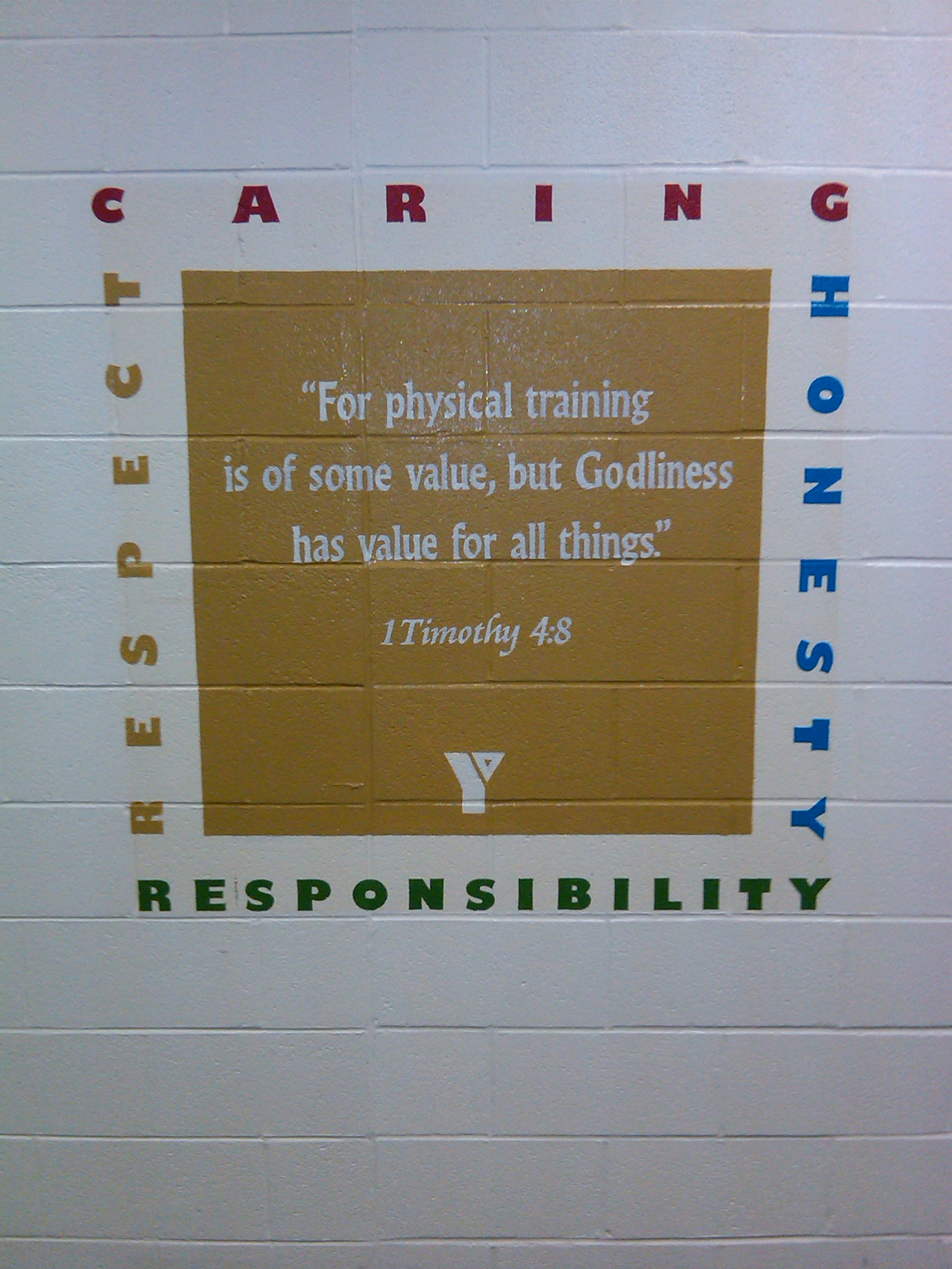 the core values are painted onto a wall of a fitness centre in a ymca along with a bible verse as well as the logo of the ymca