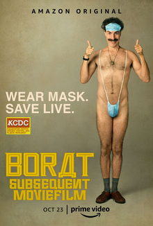 "Baron Cohen as Borat in a speedo in the style of a surgical mask, smiling and giving thumbs up. Text surrounding him says ""WEAR MASK. / SAVE LIVE.""."