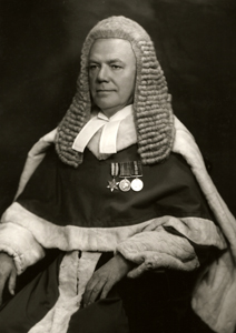 Judge in wig and gown, wearing medals
