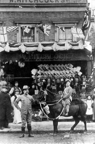 "William Hitchcock, probably with his first son, William, outside the family shop in London, c. 1900; the sign above the store says ""W. Hitchcock"". The Hitchcocks used the pony to deliver groceries. William Hitchcock with boy and pony, c. 1900.jpg"