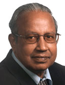 Portrait of a middle-aged Indian man with grey hair wearing spectacles and a suit and tie.