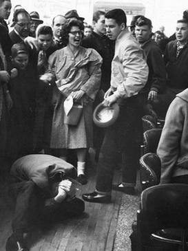 A man is curled up on the floor protecting his head with his hands while his attacker hovers over him and a crowd of bystanders watch.