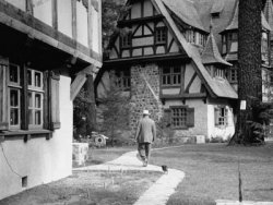 A monochrome photograph of a large man walking away from the viewer, accompanied by a small dog, walking between two buildings with half-timbered architectural styling.