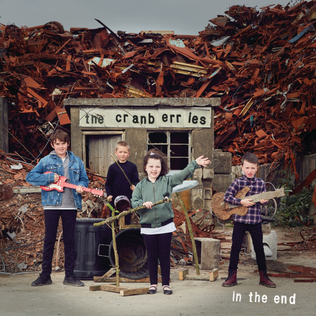A rock band made up of children performing in front of a pile of junk